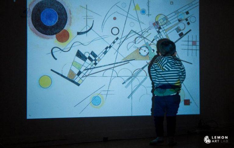 Niño con una videoproyección de arte abstracto