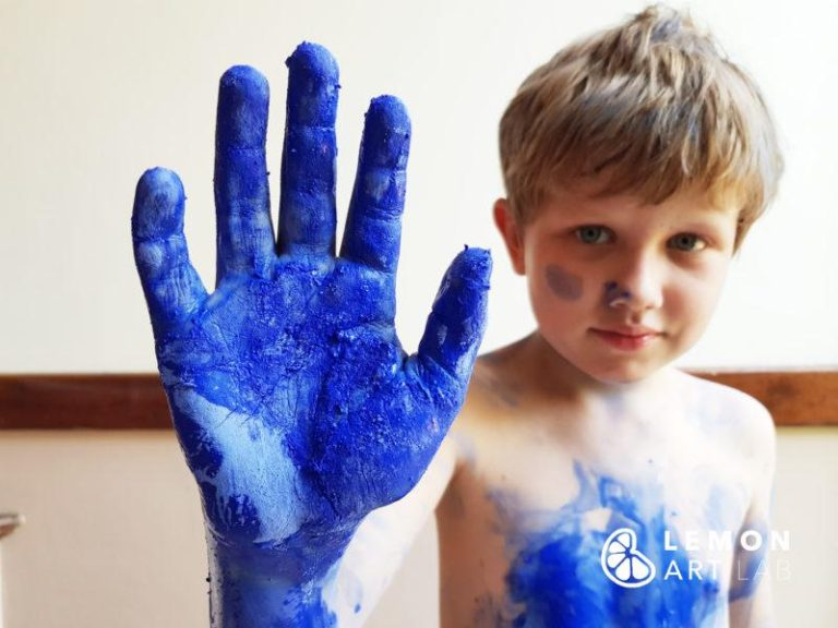 Niño jugando con pigmento azul Klein