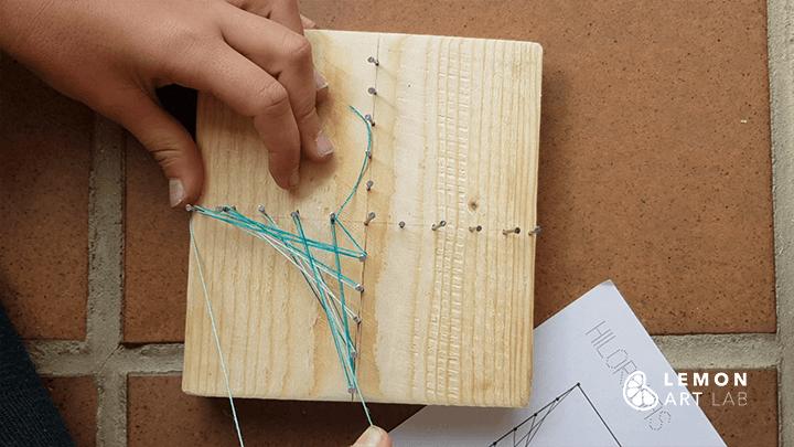 Niño trabaja con madera para crear su obra de arte
