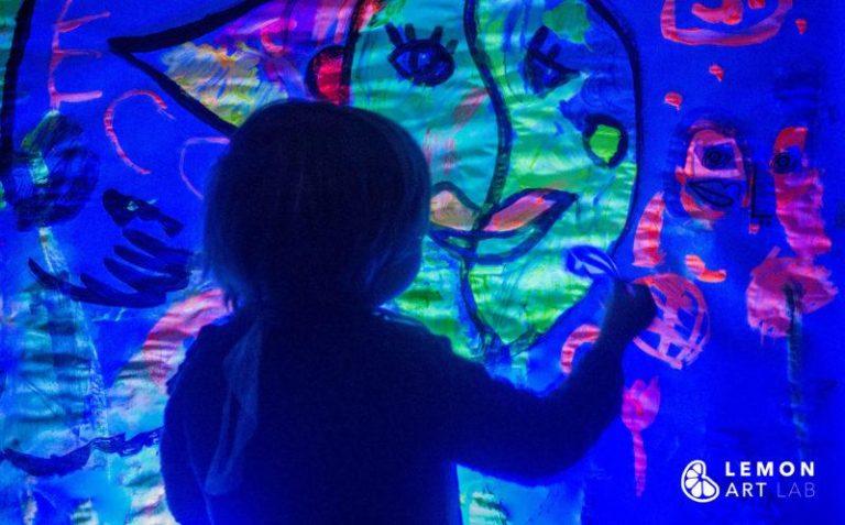 Bebé frente a un mural cubista con colores neón