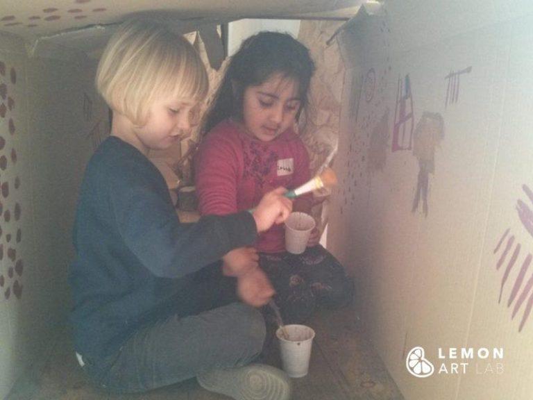 Niños hacen arte prehistórica en una instalación de juego