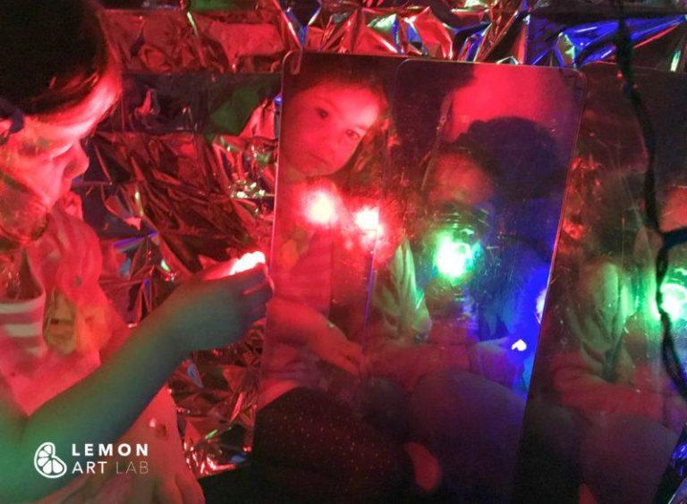 Niños exploran una instalación artística con reflejos