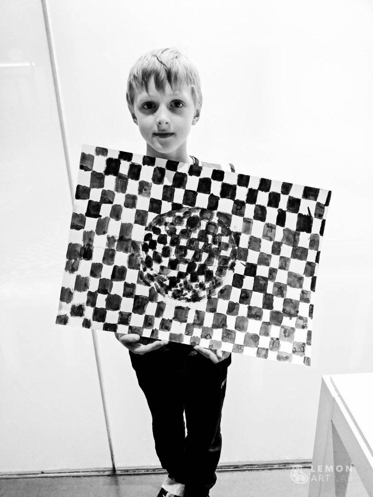 Niño muestra su pintura de patrones matemáticos