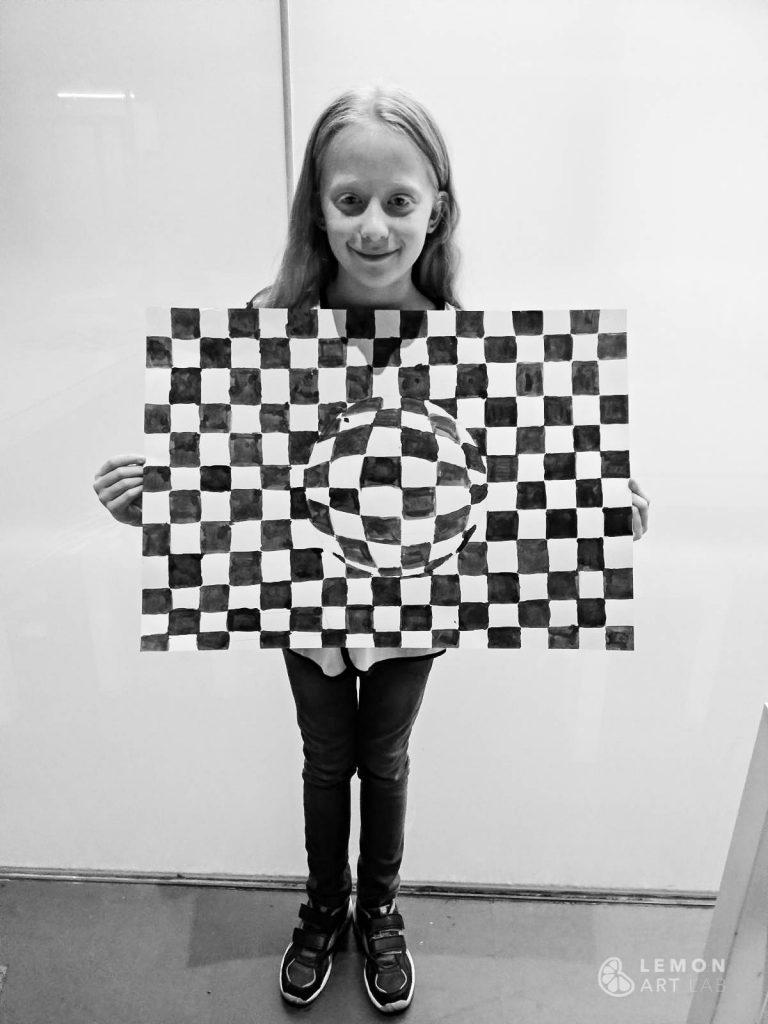 Niña muestra su obra de arte óptico