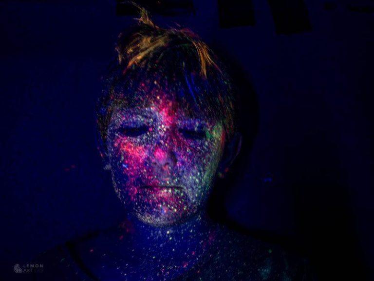 Jóven posando con pintura fluorescente en la cara