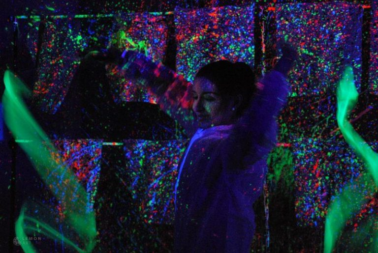 Jóvenes bailando en una sala de luz negra