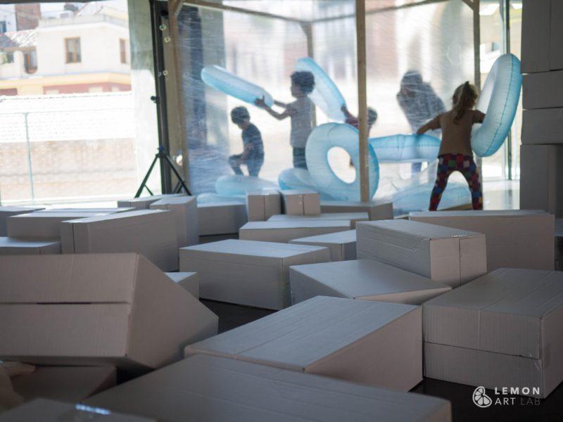 Niños juegan dentro de una obra de arte