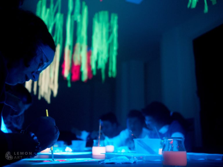 Adolescentes trabajan con pintura ultravioleta