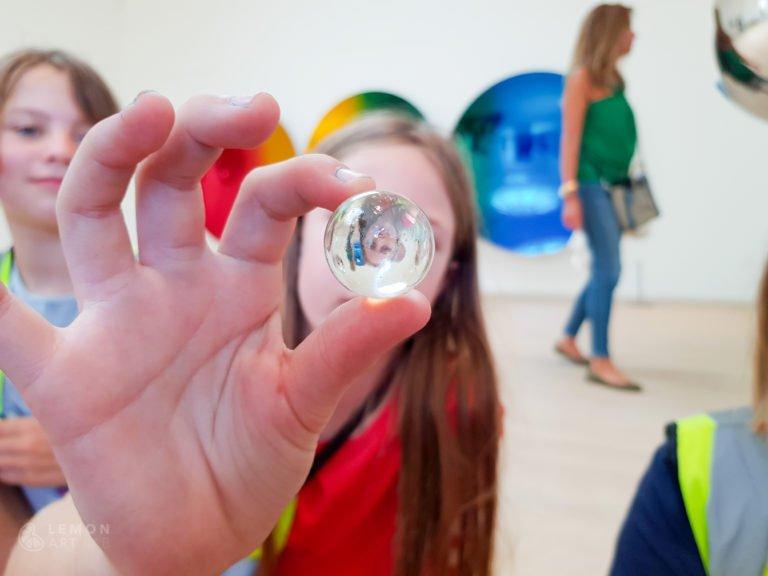 Niño enseña una canica en una galería de arte