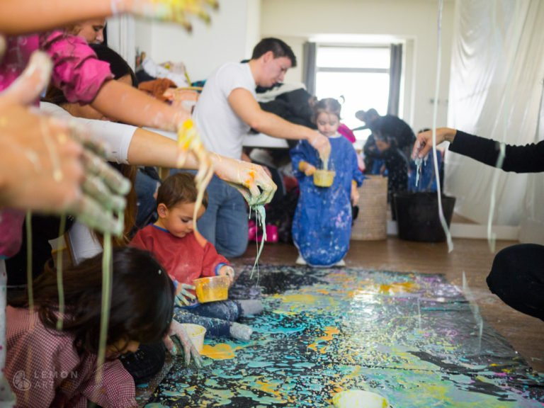 Familias crean un mural de pintura de acción