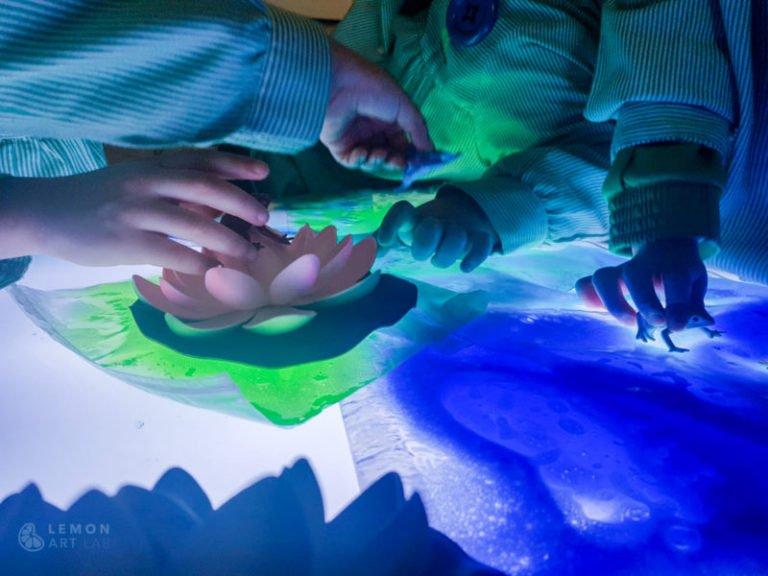 Niños de preescolar juegan con nenúfares y mesas de luz
