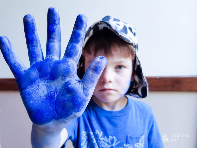 Niño con pigmento azul klein en su mano