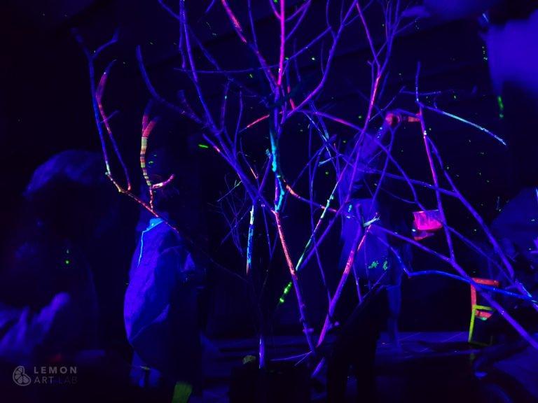 niños pintando en un bosque fluorescente