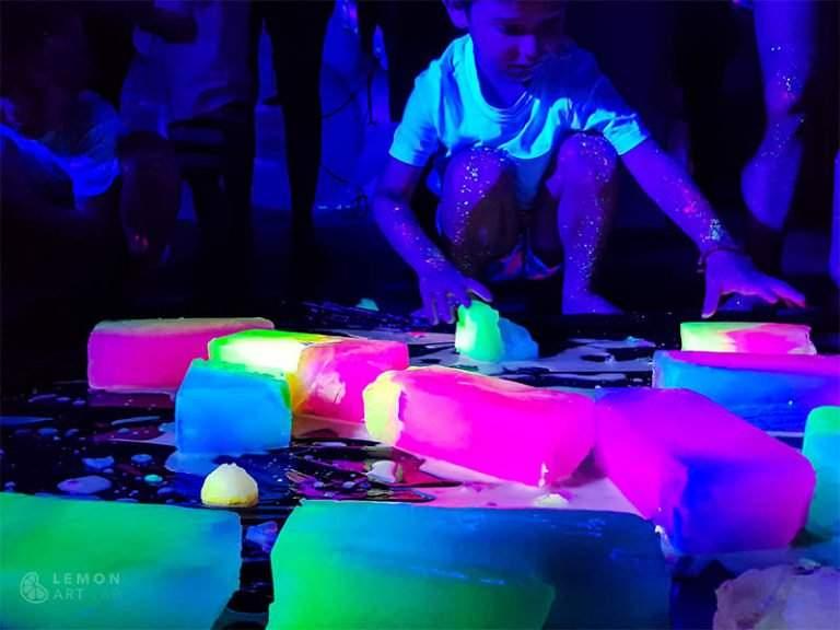 Niño juega con hielo fluorescente